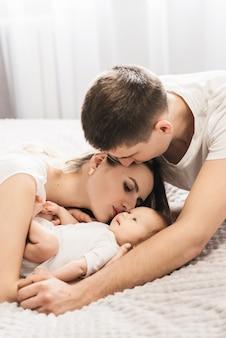 新生児を抱く女と男。ママ、パパ、赤ちゃん。閉じる。手に新生児と笑顔の若い家族の肖像画。背景に幸せな家族。