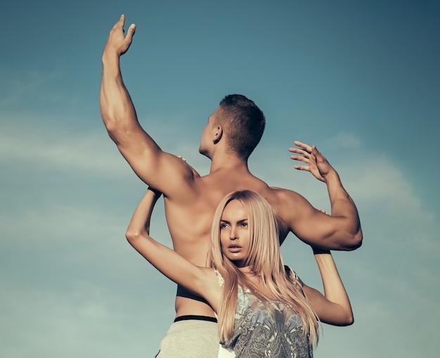 青い空に手をつないでいる女性と男性。