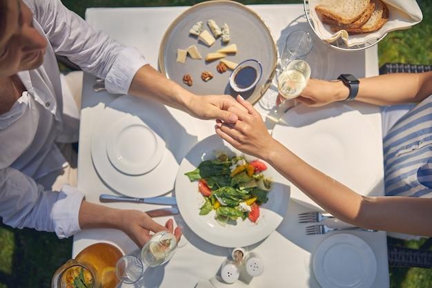 와인 잔과 함께 식탁에 앉아있는 동안 여자와 남자가 함께 손을 잡고