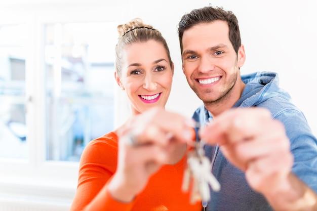 여자와 남자 자랑스럽게 집 또는 집 열쇠를 들고