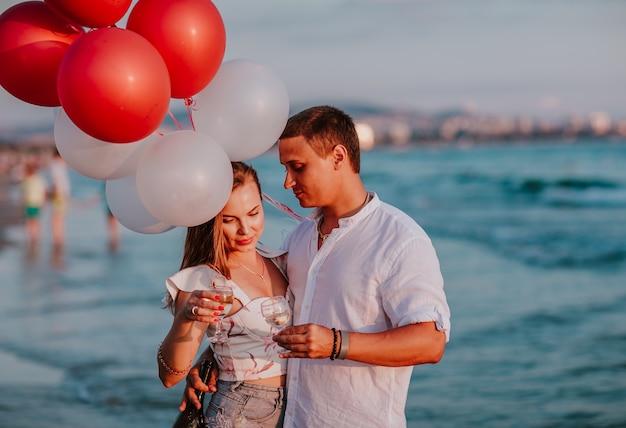 海岸でシャンパンと風船を持って抱き合って祝う女性と男性。