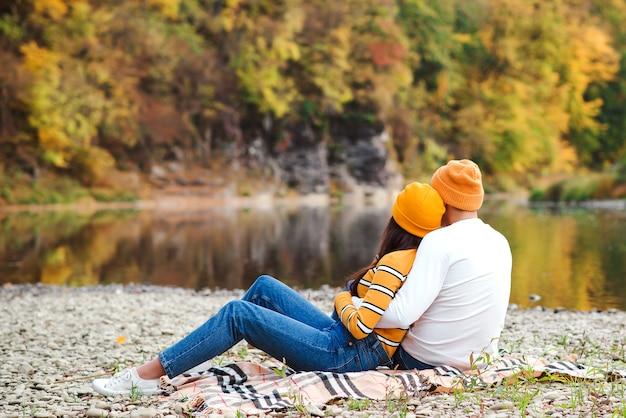 秋の公園で抱き締める女性と男性、背面図。愛、反逆、ライフスタイル。秋の気分、休暇。秋を楽しむ恋のカップル。自然の中を散歩するファッショナブルなカップル。