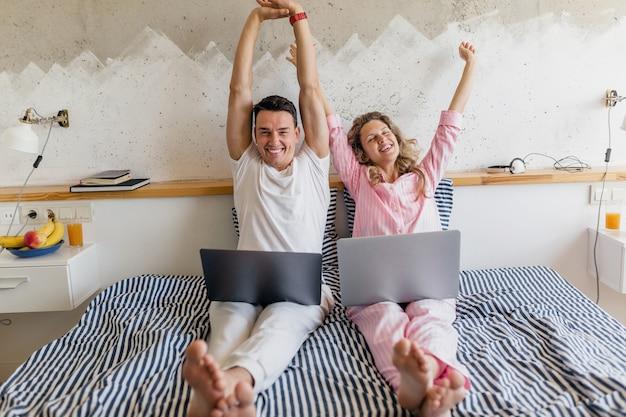 아침에 침대에서 여자와 남자가 행복한 온라인 작업 미소, 잠옷을 입고 침실에서 함께 사는 가족