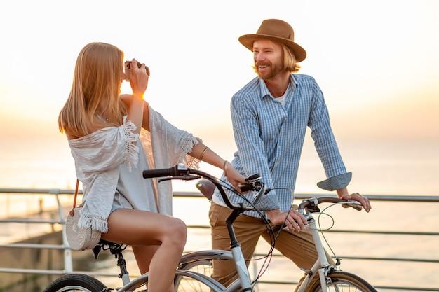Женщина и мужчина в любви, путешествующие на велосипедах на закате моря