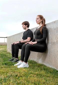 Женщина и мужчина в спортивной одежде, упражнения на открытом воздухе