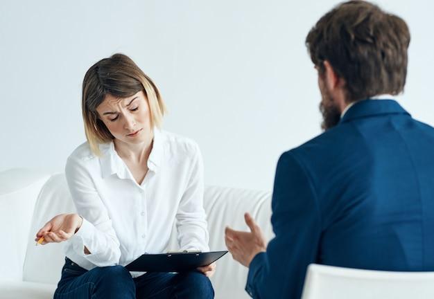 정장을 입은 여자와 남자는 실내에서 직장에서 뭔가를 논의하고 있습니다. 고품질 사진