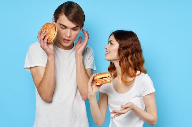 白いtシャツの女性と男性ファーストフードダイエット青い背景