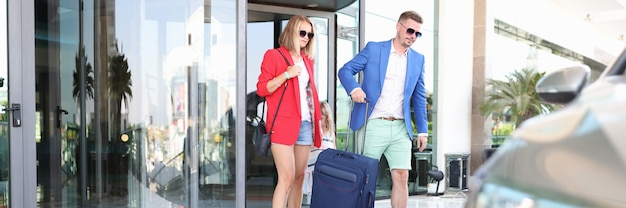 女性と男性はスーツケースを持って建物を出ます。