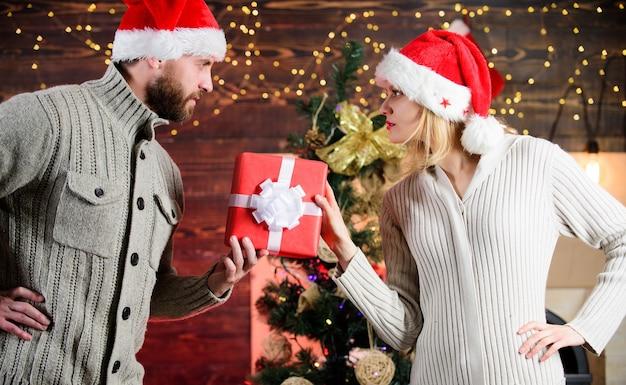 女性と男性はクリスマスプレゼントが大好きです。一緒にクリスマスを祝います。冬季セール。愛のサンタ帽子のカップル。プレゼントの時間。あけましておめでとう。家族の休日。月に戻ってあなたを愛してください。