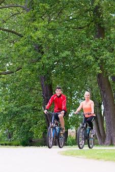 여자와 남자는 숲에서 산악 자전거에