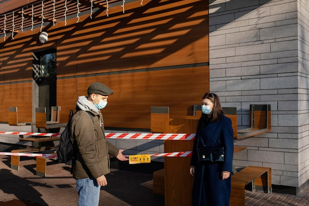 マスクを身に着けている通りの女性と男性