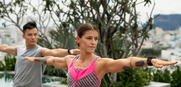 Женщина и мужчина на открытом воздухе практикуют позу йоги
