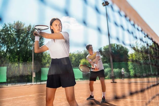 ダブルステニスで遊ぶ女性と男性