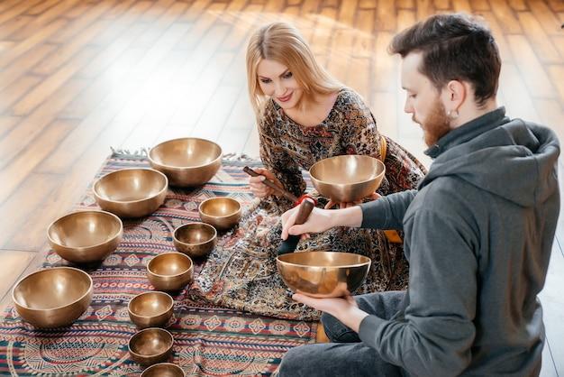 Женщина и мужчина играют на тибетской поющей чаше для сидения звуковой терапии