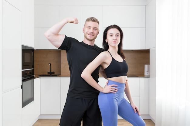 Женщина и мужчина позирует перед камерой, два спортсмена по фитнесу на кухне дома