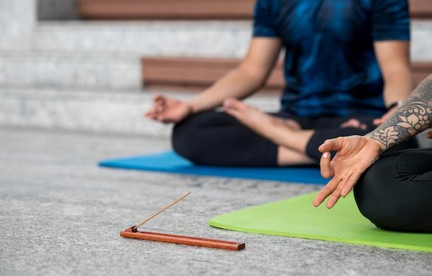 Женщина и мужчина практикуют йогу на коврике рядом с шагами