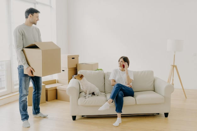 Женщина и мужчина арендаторы недвижимости ставят в пустой гостиной, женщина сидит на диване в середине комнаты