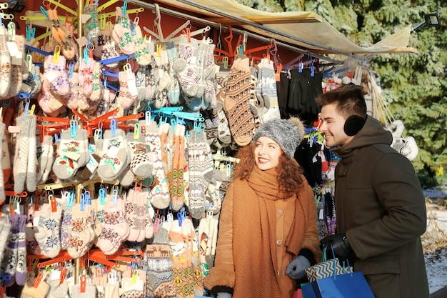 クリスマスマーケットで買い物をする女性と男性