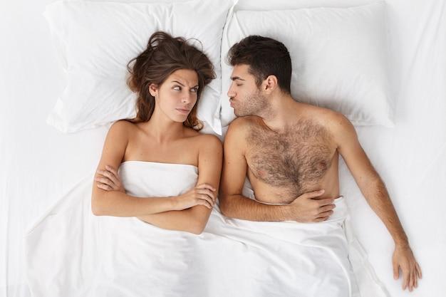 Женщина и мужчина, сидя в постели, вид сверху