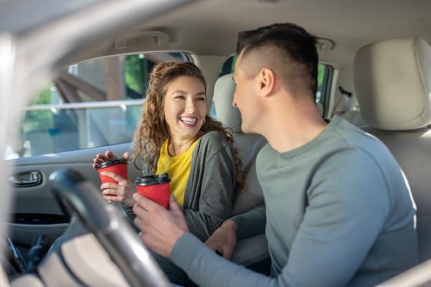女と男のコーヒーのグラスが付いている車に座っています。