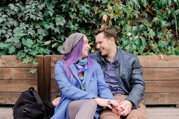 Женщина и мужчина улыбаются и обнимают друг друга на улице