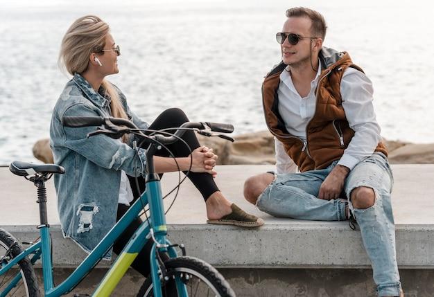 Женщина и мужчина разговаривают рядом с велосипедом