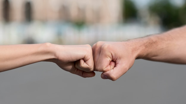 女と男が拳に触れる