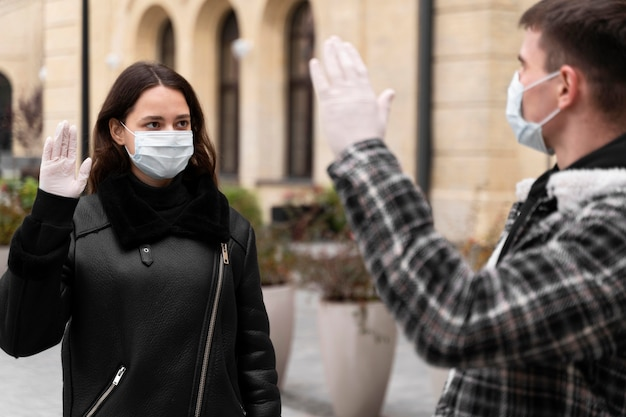 Женщина и мужчина машут альтернативными приветствиями на открытом воздухе