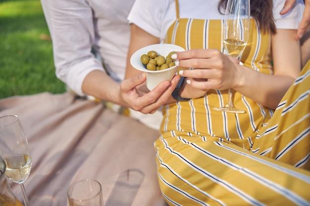여자와 남자는 그들의 손에 녹색 올리브와 함께 접시를 들고 흰색과 노란색 옷을 입고