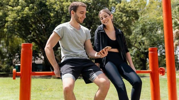 운동하는 동안 야외에서 스마트 폰으로 여자와 남자