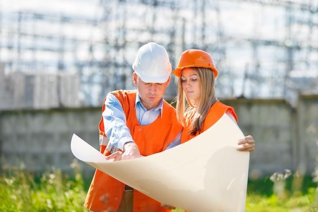건설 현장에서 건축가로 일하는 여자와 남자