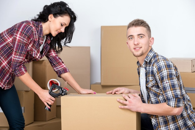 Женщина и мужчина, оборачивая коробки, пока они двигаются домой.
