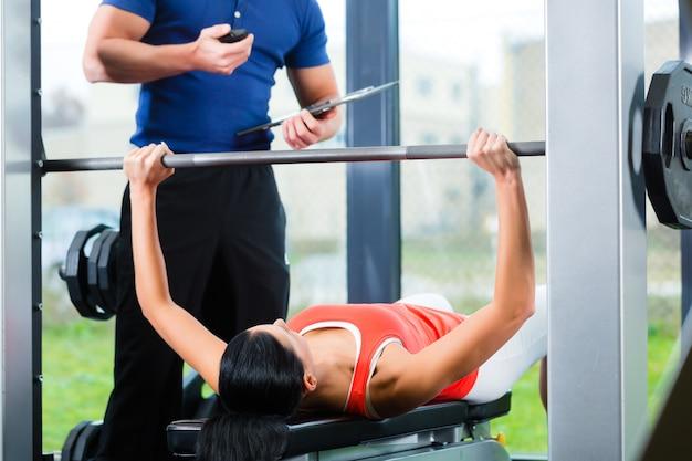 Женщина и личный тренер в тренажерном зале