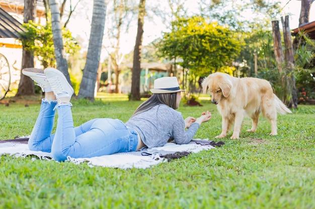 庭の女性とペット。屋外で遊ぶラブラドールレトリバー。ペットとアウトドアのコンセプト。