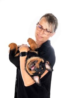 Женщина и щенок ротвейлера на белом фоне