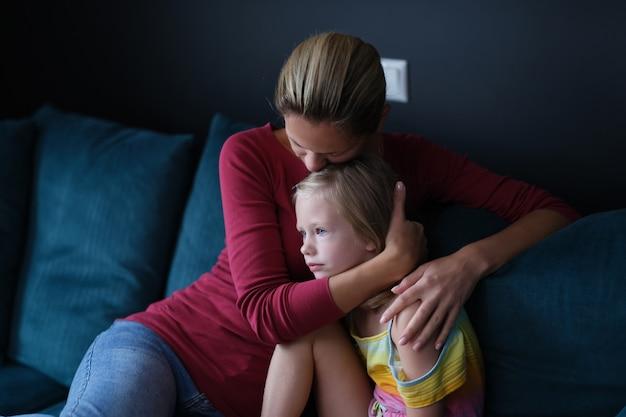 女性と悲しい小さな娘がソファに座って抱きしめています
