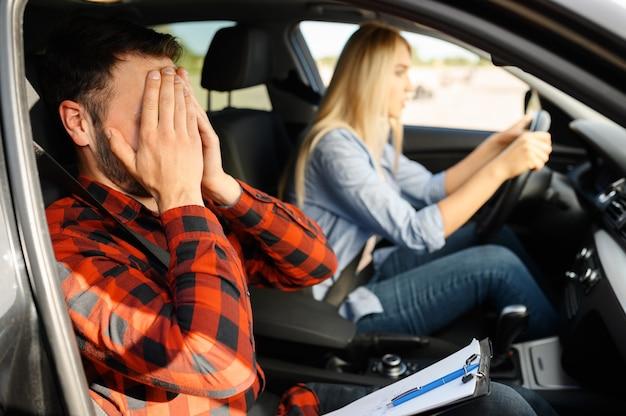 Женщина и испуганный инструктор в машине, автошколе. мужчина учит леди водить автомобиль. образование водительского удостоверения