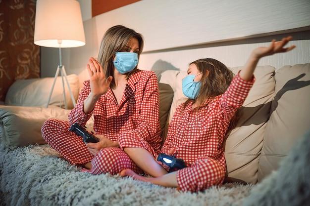 Женщина и молодая девушка в пижаме и медицинской защитной маске