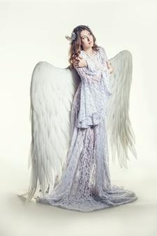 Женщина-ангел с костюмом белых крыльев в религиозном смысле