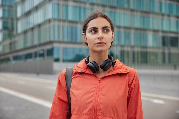 Woman in anorak strolls outdoor has regular sport training to prevent negative mood and stay healthy has daily workout and exercises outdoor being active in good physical condition
