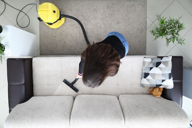 Woman in apartment cleans sofa with vacuum cleaner