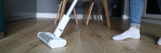 The woman in apartment washes the floor with mop