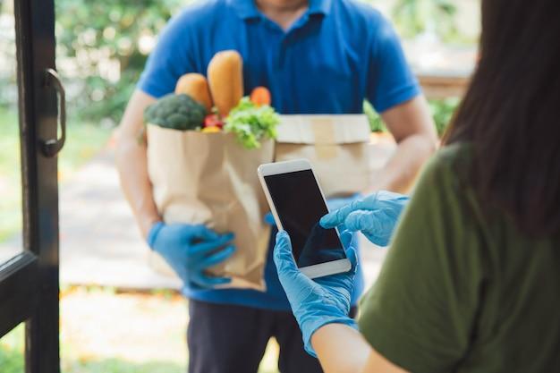 食料品店の配達後にデジタル携帯電話で署名を追加する女性