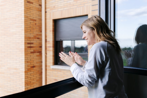 Woman applauding from her balcony to support those fighting coronavirus