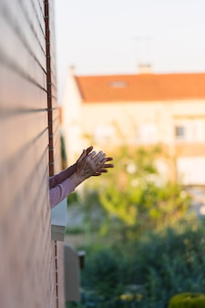 コロナウイルスと戦う人々に感謝する家から拍手する女性