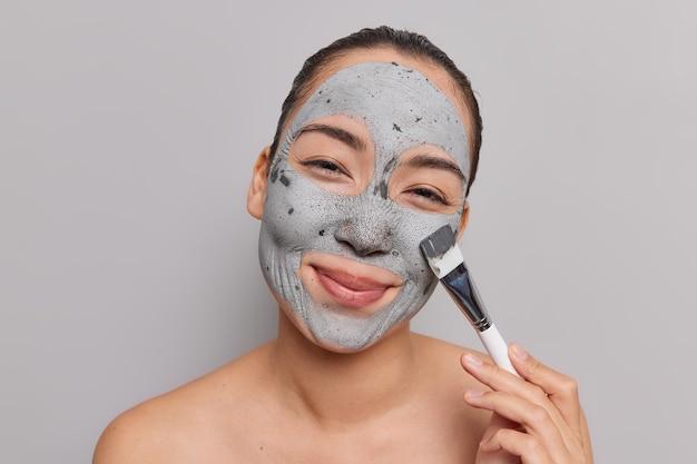 여자는 피부 회춘을 위해 점토 마스크를 적용하고 화장용 브러시는 회색으로 격리된 벌거 벗은 어깨를 즐긴다