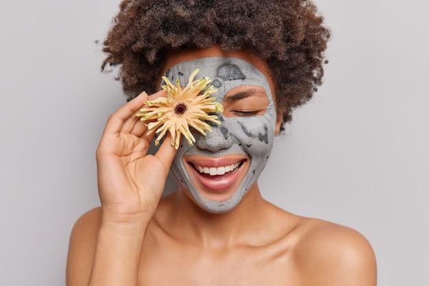 피부 회춘을 위해 얼굴에 점토 마스크를 바르는 여성은 회색으로 격리된 천연 화장품 성분을 사용하여 눈에 꽃을 들고 있다