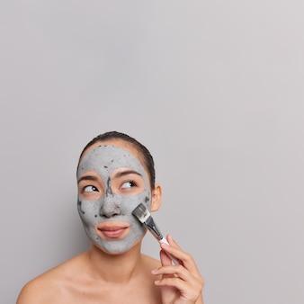 여자는 얼굴에 점토 마스크를 바르고 화장용 브러시를 들고 회색으로 벗은 안색 포즈를 돌본다