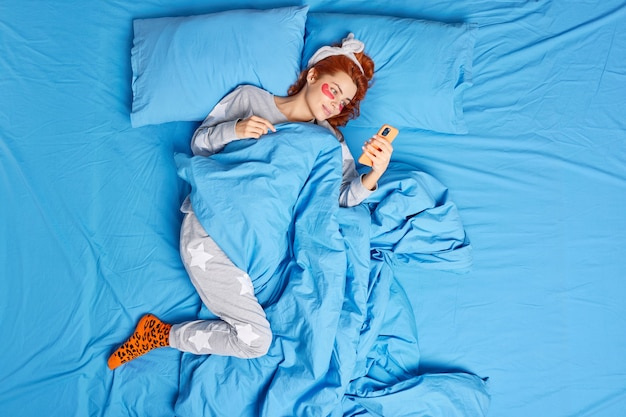 Woman applies collagen patches lies in bed uses smartphone scrolls social networks wears pajama coned with blanket.