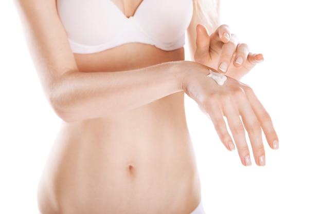 女性は白い背景の上の彼女の手にクリームを適用します